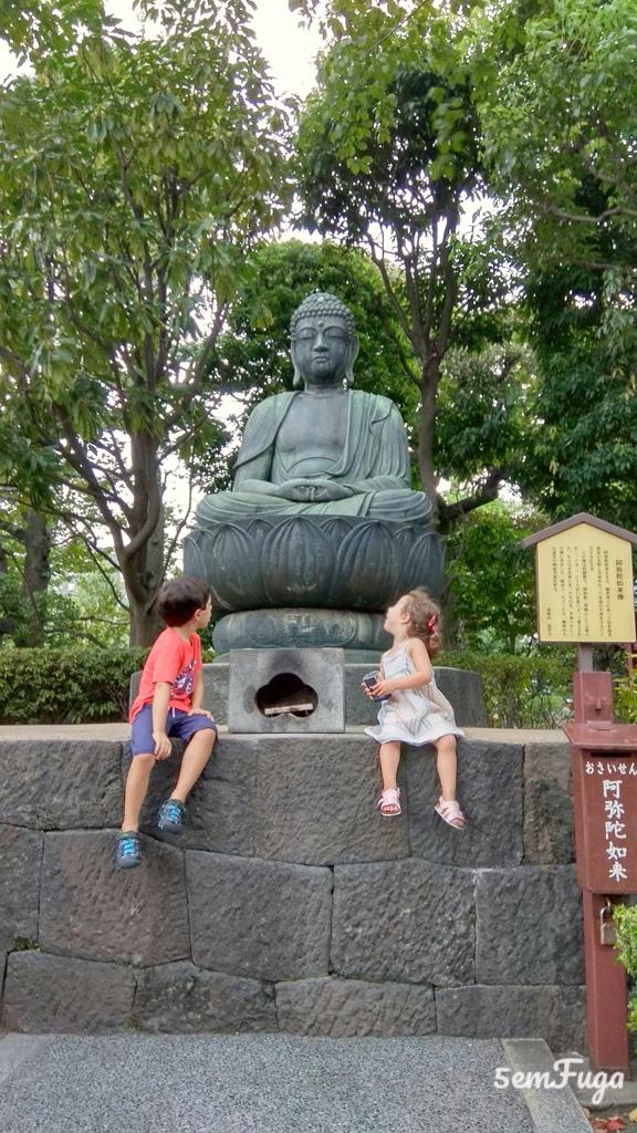 crianças sentadas junto a estátua de Buda em Asakusa
