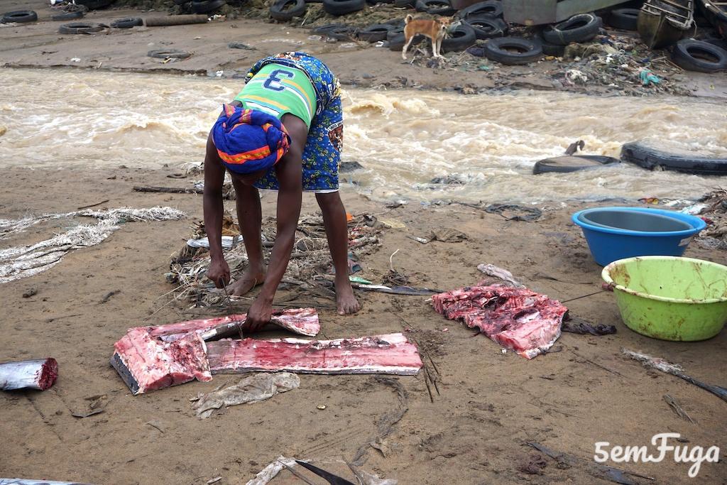 mulher a cortar peixe com catana na areia da praia melão