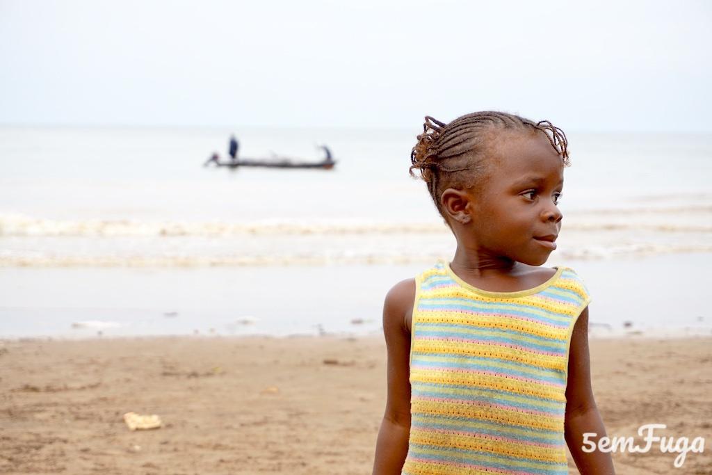 criança na areia na praia melão com uma piroga atrás no mar