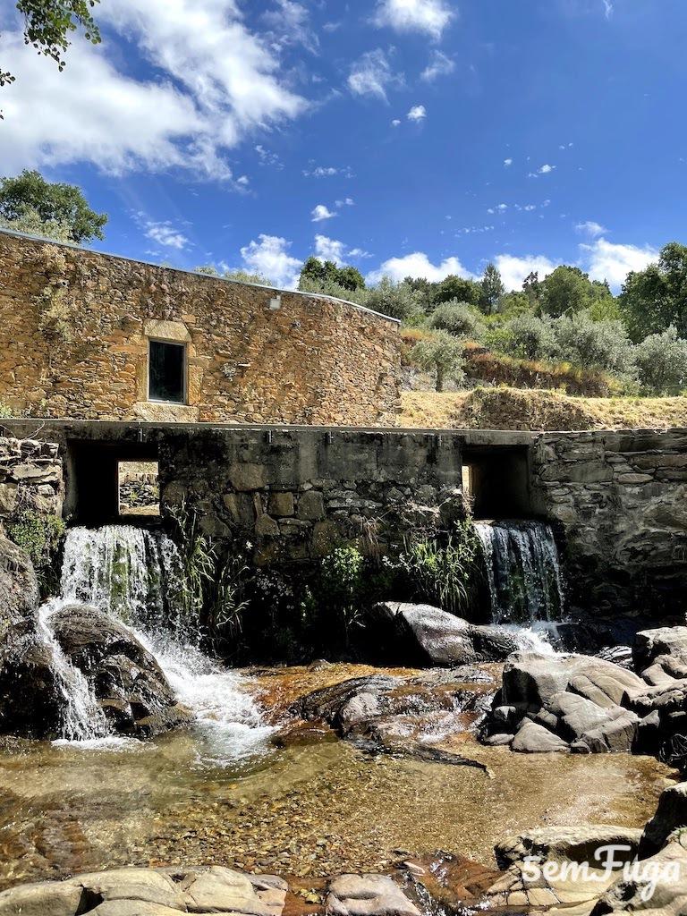 água a cair em cascata pelas comportas abertas da piscina fluvial